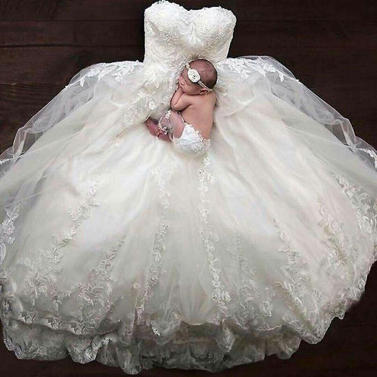 Newborn laying on wedding dress