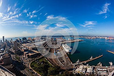 Colorful wide angle photo image overlooking Durban harbor port city on the indian ocean east coast South-Africa. Looking east at harbor entrance beach buildings and large car vehicle export import terminal, ships railway lines infrastructure.