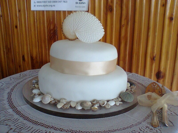 Nautilus shell topped wedding cake. Family recipe choc cake choc ganache and fondant with satin ribbon and real shell borders