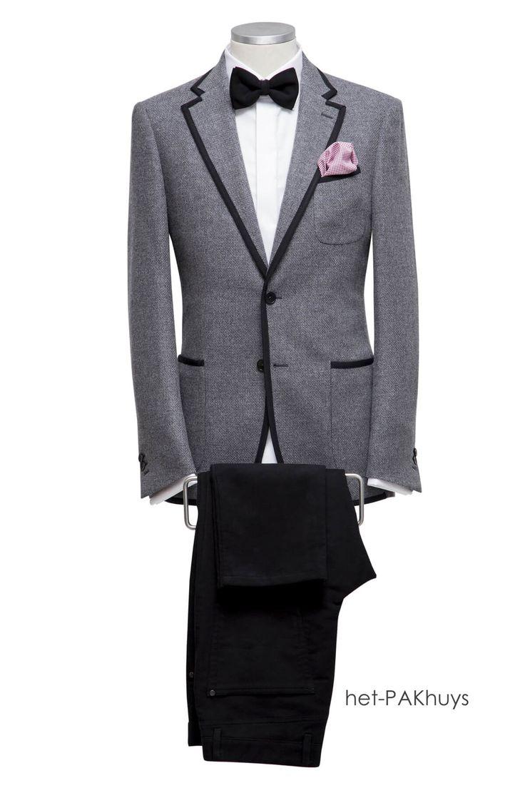 Maatkostuum gemaakt van grijze flannel, revers en zakjes afgewerkt mat zwarte band . Bijpassende pantalon en wit maatoverhemd met blinde sluiting