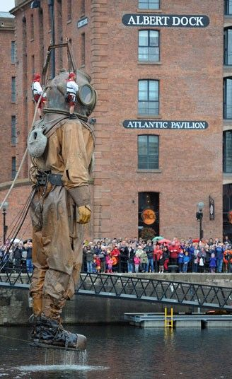 Giant puppet Sea Odyssey Giant Uncle emerges in Liverpool--part of an event honoring the anniversary of the sinking of the Titanic