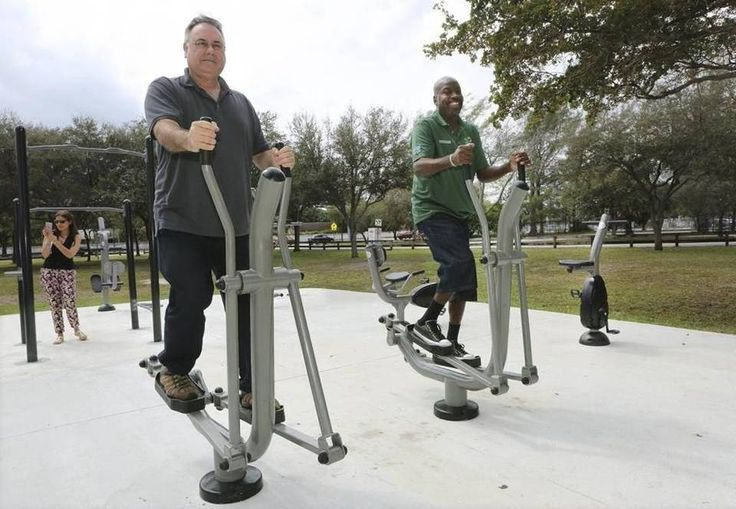David Livingstone, left, and Mitch Burroughs, employees of Miami-Dade's parks department, use the elliptical machines at Miami-Dade Parks' new Fitness ZoneAE outdoor gym in Aventura.