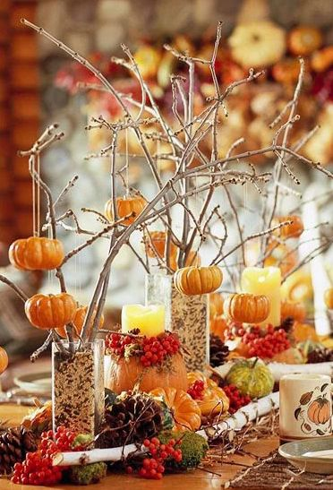 DIY Thanksgiving Table Centerpiece...paint some small branches white and put them in tall clear glasses with candy corn, popcorn kernels, etc. to anchor them. Hang craft store mini pumpkins from the branches and decorate around the glasses with leaves, pine cones, pumpkins, gourds, or any fall items.