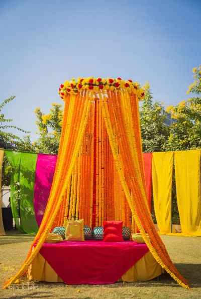 Mehendi Decor - Marigold Mehendi Decor | WedMeGood | Genda Phool Decor with Pink and Yellow Decor Detailing #wedmegood #indianbride #indianwedding #bridal #mehendidecor #decor #diydecor #marigold