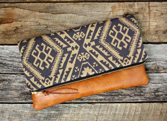 Made to order. Ships out 2 to 4 days after purchase.  This foldover clutch has an eye-catching blue and tan ikat fabric design with a copper brown faux leather for the bottom. It also has a faux leather pull attached to the zipper for easy opening.  This is the perfect size to carry your items in: your cell phone, keys, make-up, money, small camera, wallet, or blackberry and room for your kindle or iPad. Dont want to carry a big bulky purse? This is the perfect size to grab and go for a day…