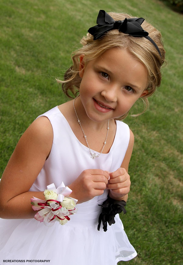 Flower girl in white with a black bow headband and a wrist corsage