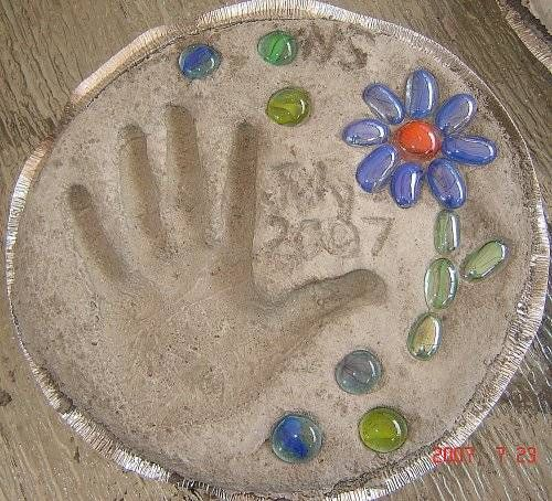 Stepping stone with handprint, flat marbles from Dollar Store, made in disposable aluminum pan used as mold.