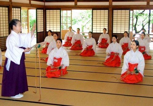 神社音楽協会の先崎径子代表理事から指導を受ける巫女たち=太宰府市の太宰府天満宮