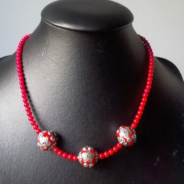 #halsketting van rode koraalkraaltjes met enkele metalen kralen en een dikke metalen kashmirikraal 20€