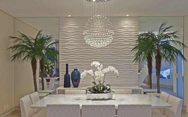 O revestimento em 3D traz movimento e contrapõe a sofisticação dos espelhos laterais na sala de jantar