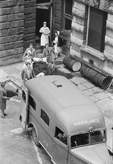 """GUY'S HOSPITAL LIFE LONDON HOSPITAL ENGLAND 1941 (D 2344). A casualty is carried on a stretcher to a waiting ambulance at Guy's Hospital in London. The ambulance """"was presented to American Ambulance Great Britain by Fred A Poor of Chicago USA, June 1940"""". (During the Blitz, World War Two)"""