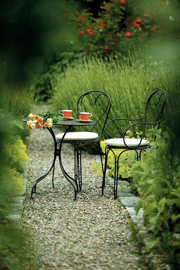 petit coin repas dans le jardin aménagé avec une table ronde et deux chaises en fer forgé noir