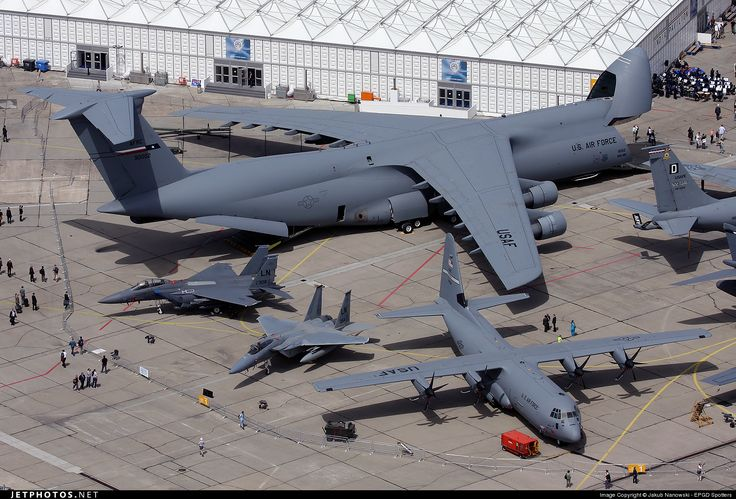 Lockheed C-5 Galaxy in comparison with other military aircraft, including which looks like a Hercules C-130 at the wing tip.