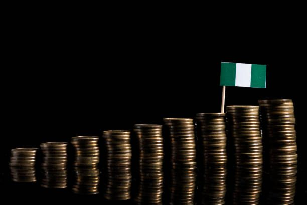 nigerian flag with lot of coins isolated on black background