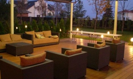 На участке соорудили патио под накрытием. Для патио используют деревянное покрытие. На площаде разместили садовую мебель, которая может выдержать перепады температур и осадки. Освещают территорию у...