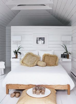 Beach stye bedroom with raffia cushions, reclaimed wood slat wall and divine use of a small space