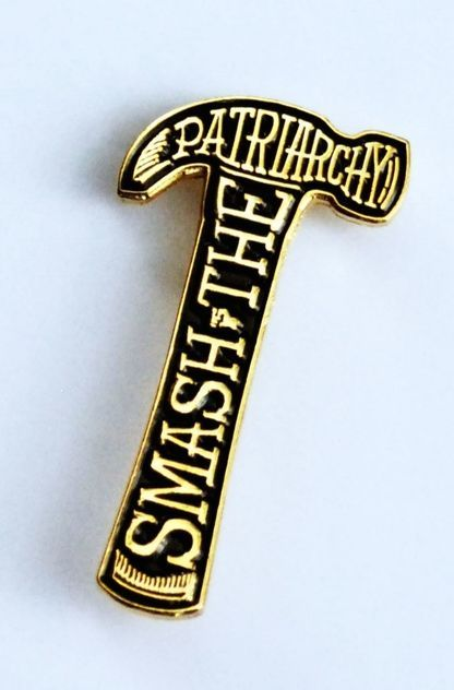 Gold metallic and black enamel Smash the Patriarchy Lapel Pin measures 1.5 inches long and has a hard rubber back. A collaboration of Bang-Up Betty andAshlee N