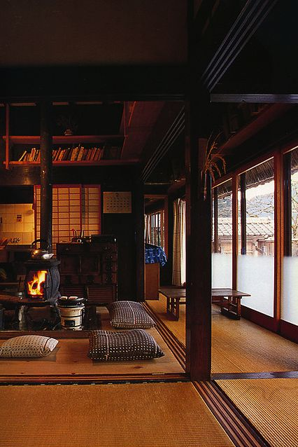 Japanese farmhouse interior with wood stove to replace traditional sunken hearth (irori).