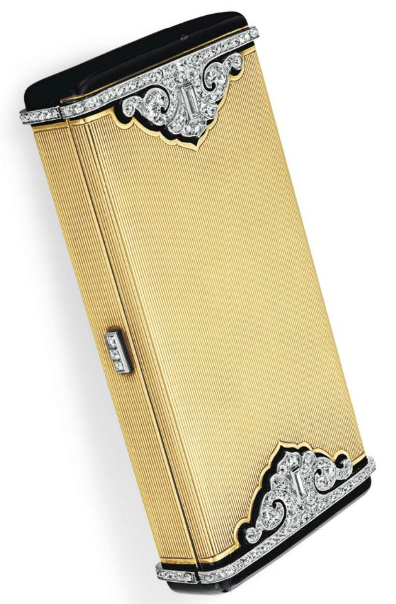AN ART DECO DIAMOND, ENAMEL AND GOLD VANITY CASE, BY CARTIER. Of rectangular outline, the gold ribbed onyx case enhanced with old European and baguette-cut diamonds within a black enamel border, the square-cut diamond pushpiece opening to reveal a mirror, two concealed compartments and a lipstick case, mounted in gold, circa 1925, 3 1/4 x 1 5/8 x 1 3/16 ins., circa 1925, signed Cartier. #Cartier #ArtDeco #vanity