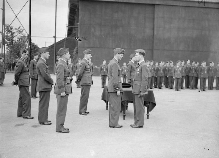 """P/O John L """"Johnny"""" Allen of No 54 Squadron RAF receives the DFC from King George VI at RAF Hornchurch on 27 June 1940. The award came on 11 June in recognition of the rescue of S/L Francis L """"Drogo"""" White on 23 May when Allen and P/O Alan C """"Al"""" Deere accompanied F/L James A """"The Prof"""" Leathart to pick up the CO of No 74 Squadron RAF from Calais-Marck. Allen and Deere destroyed 3 and badly damaged 3 more. Allen downed 1 and damaged 2 others in Spitfire Mk I KL-A."""