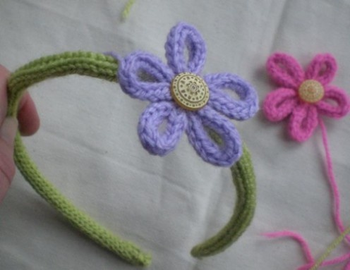 Made with a headband, pipe cleaner, a button and knitting nancy.  Sorry no instructions.