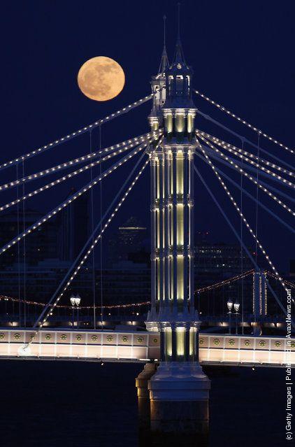 Luna llena se eleva sobre Albert puente en Londres