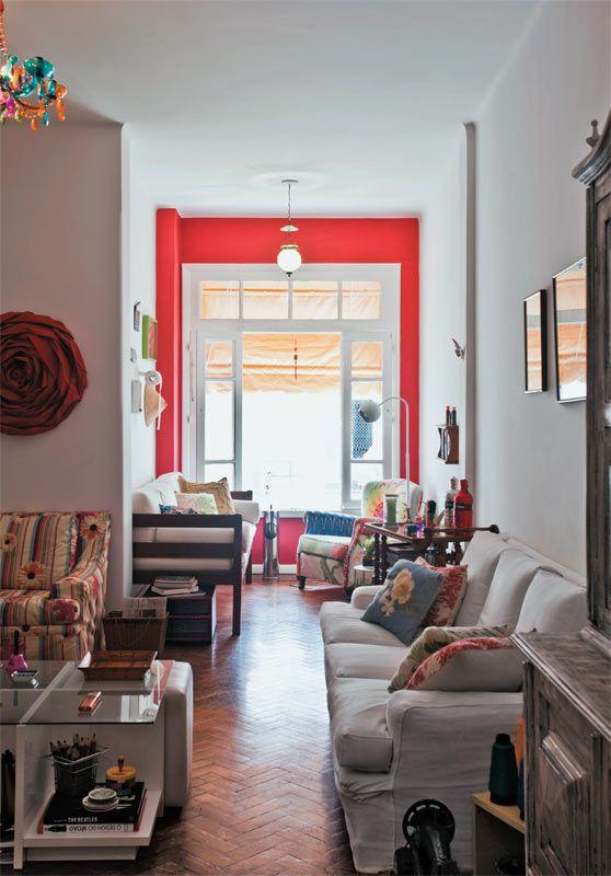 A parede que emoldura a única janela do cômodo foi destacada com um vermelho aberto (Melancia, ref. P 112, da Suvinil). Neste espaço, até um sofá de estilo balinês encontrou lugar.Mesa de centro. Com 77 x 77 x 42 cm*, a Zoom leva tampo de vidro sobre estrutura de MDF branco. Toque a Campainha , 10 x R$ 29.