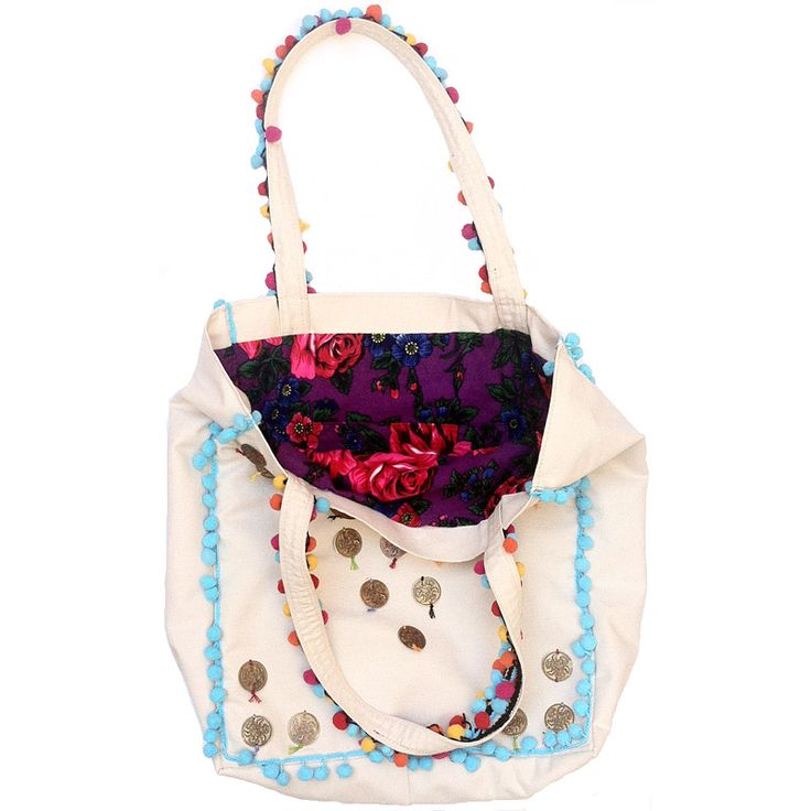 This Upheld Handmade Beach Bag is uniquely designed & made of white fabric with sewed coins, bright tassels, a light-blue braid, and a colorful lining.