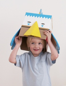 For this playful bird mask, you'll only need two cardboard boxes (one larger than your child's head) and colored
