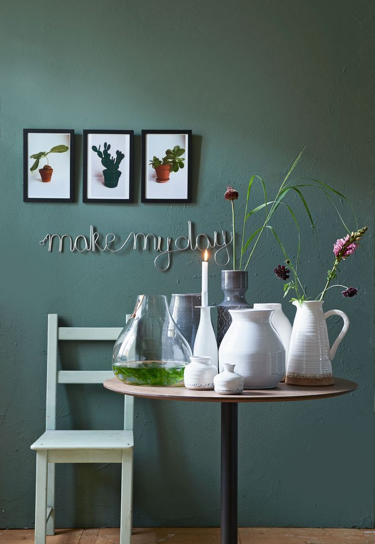 Table with small and large vases and posters of plants on the green wall | Styling Fietje Bruijn | Photographer Dennis Brandsma | vtwonen catalog autumn 2015 | #vtwonencollectie