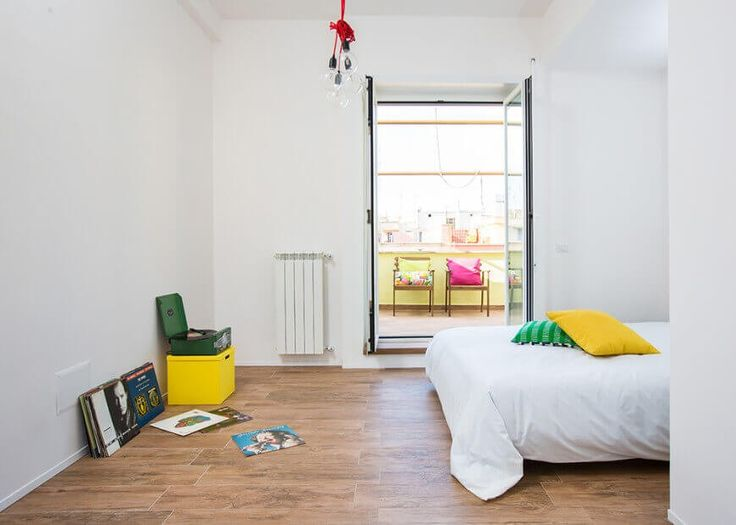 Hier haben wir das Hauptschlafzimmer, ein minimalistisches Leerraum mit viel Platz für Aktivitäten. Des Eigentümers Schallplattensammlung sitzt zusammen mit einem kühnen gelben Feld nach links, während wir auf die Terrasse durch Doppeltüren sehen kann.