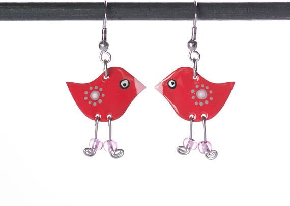 These cute little enamel bird earrings are happily singing to each other. Gorgeous in their red spotty polka dot feather coats, the hand painted whimsical dangle earrings are the perfect fun accessory for any lady.    Add a touch of whimsy to your outfit for a really fun look. Whatever the occasion, these unique red enamel bird earrings are going to wow your colleagues, friends and family. They will look fabulous no matter what you're wearing. For every day, you can wear them with a pair of…