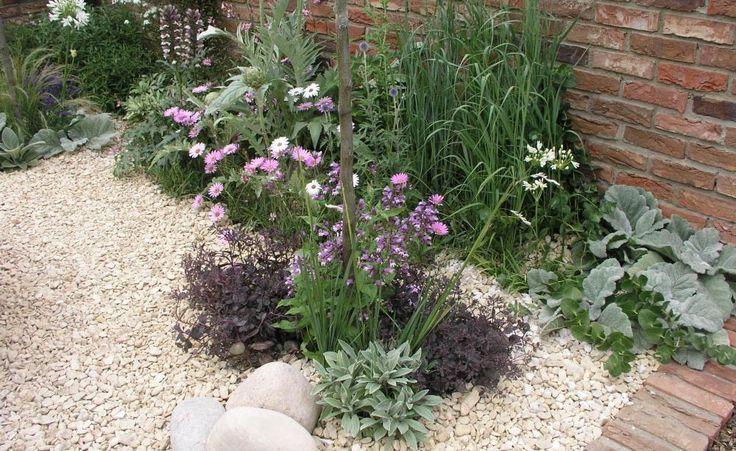 Mit Steinen lassen sich schöne Kontraste im Garten erzeugen. Hier stehen die hellen Kiesel der dunkleren Gartenmauer gegenüber