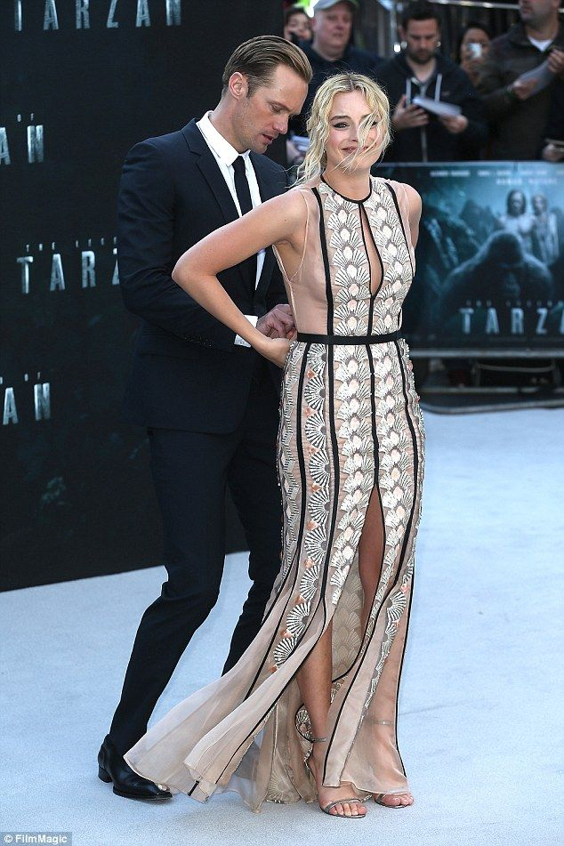 Damsel in distress: Margot Robbie plays Jane in Legend Of Tarzan but it seems life imitating art as co-star Alexander Skarsgård gives her a hand with her Miu Miu dress at the premiere.