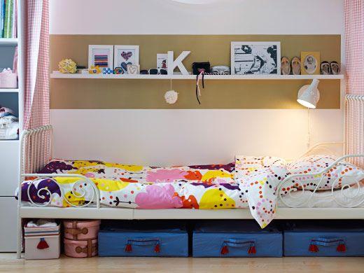 Ausziehbares MINNEN Bettgestell mit Federholzrahmen in Weiß mit SÅNGFÅGEL Bettwäsche-Set in Rosa, unter dem Bett PYSSLINGAR Bettkästen in Hellblau, über dem Bett an der Wand RIBBA Bilderleiste in Weiß mit Bildern etc. darauf
