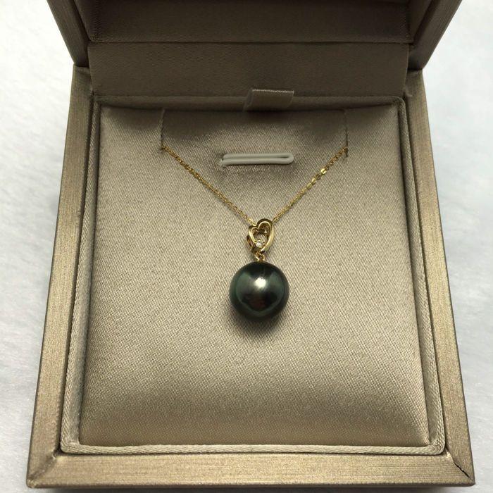 Tahitiaanse zwarte parels diamanten gouden ketting 18K. De diameter van de parel 10.8 mm.  geen minimumverkoopprijs   Tahitiaanse zwarte parel ketting parel oppervlak met een fijne diamant 18K gouden ketting.Oorsprong: Tahiti.Verscheidenheid: zee parels.Diameter: Parel 10.8 mm.Hoeveelheid: 1 parel.Gewicht: 28 g.Lengte: 42-45 cm verstelbaar.Kleur: Peacock groen.Glans: Zeer sterk.Steen: Diamond.Hoeveelheid: 1 stkGewicht: 0.016 karaat.Kleur: HScherpte: VS2Cut: ronde helder.Accessoires: 18K…
