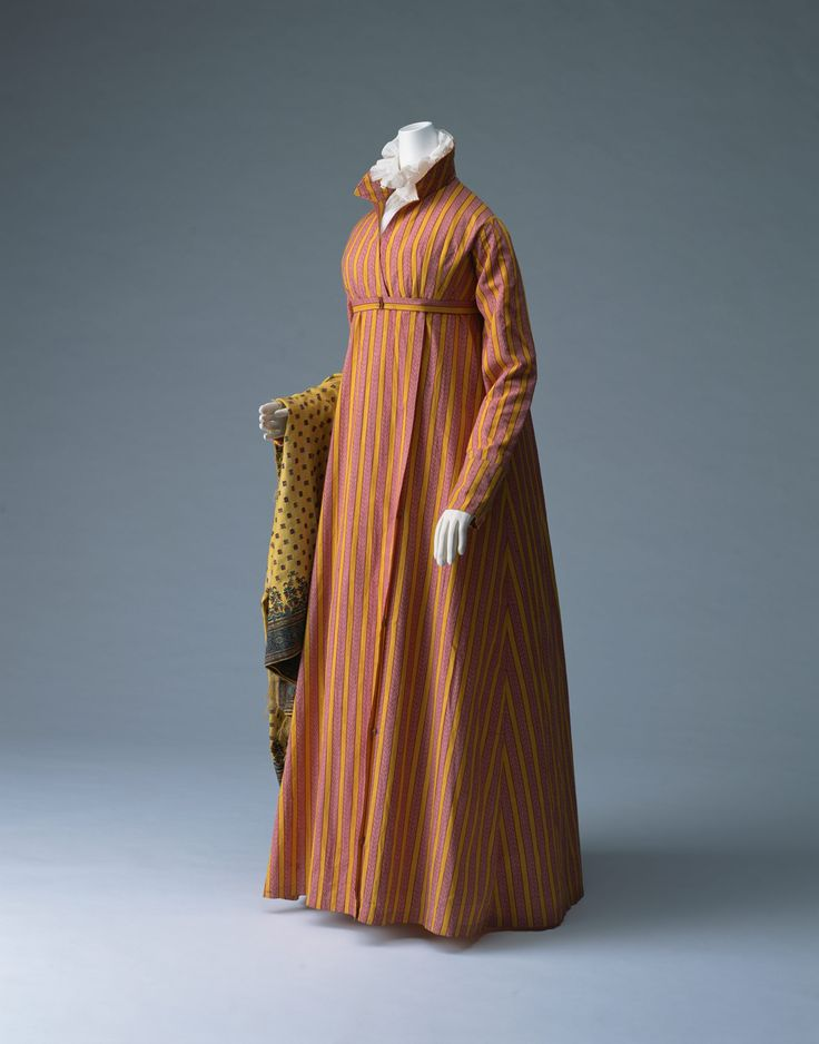Coat Dress (Redingote)1810-1815-France [Kyoto] Material: Yellow ocher and cardinal red strip printed plain-weave cotton with matching belt.  The slim silhouette of this coat dress, free of any excessive decorations, was accentuated by a striped pattern, which was popular at the time. The belt marks a high waistline, and the front-opening skirt has a fly closure. Stripes became popular a little before the French Revolution as Chinoiserie, Chinese influence.