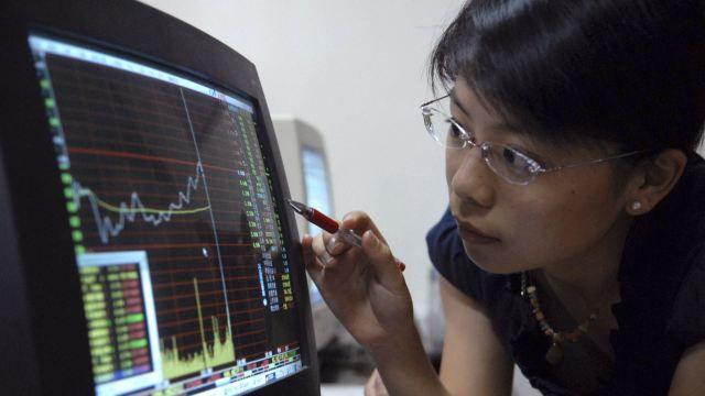 Juanjuan, a college student, checks stock information at a stock exchange in Fuzhou