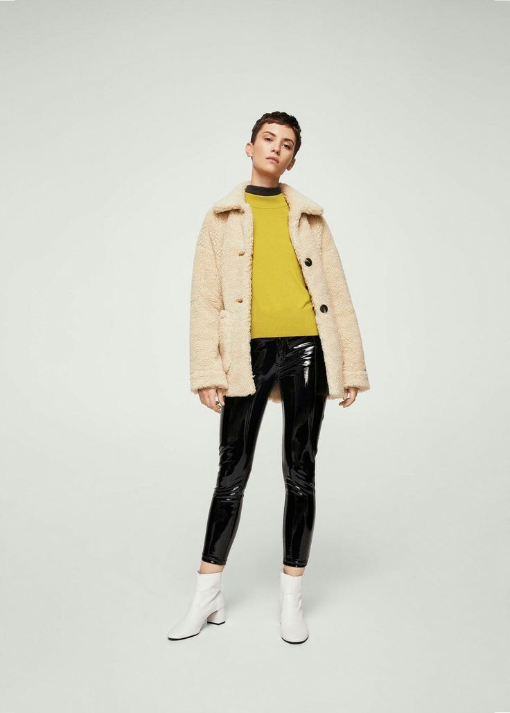 Abrigo peluche, jersey amarillo, pantalon charol negro y botas blancas
