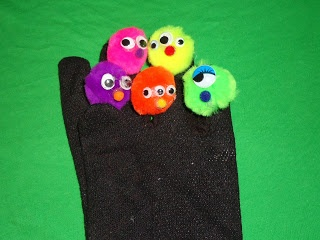 """At 4, many of our little preschoolers are a little wary of Halloween. I found this cute little fingerplay in a Mailbox magazine years ago and made these little monsters out of pom poms to go on my storytelling mitt/glove. Before I do this, we have a discussion about how monsters are not really """"real"""". I tell them the monsters in this story are imaginary, and actually, it's a silly story about how the child doesn't want to go to bed, so he tries to tell his mom that there are monsters under…"""