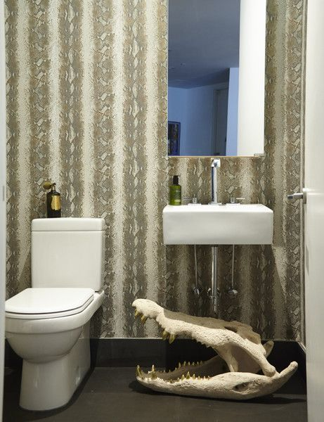 Contemporary Eclectic Bathroom: Large alligator skull below white sink and large mirror in reptile-patterned bathroom.  .