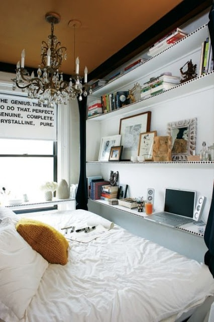 Cozy small area bedroom. The shelves with all the kinck nacks.