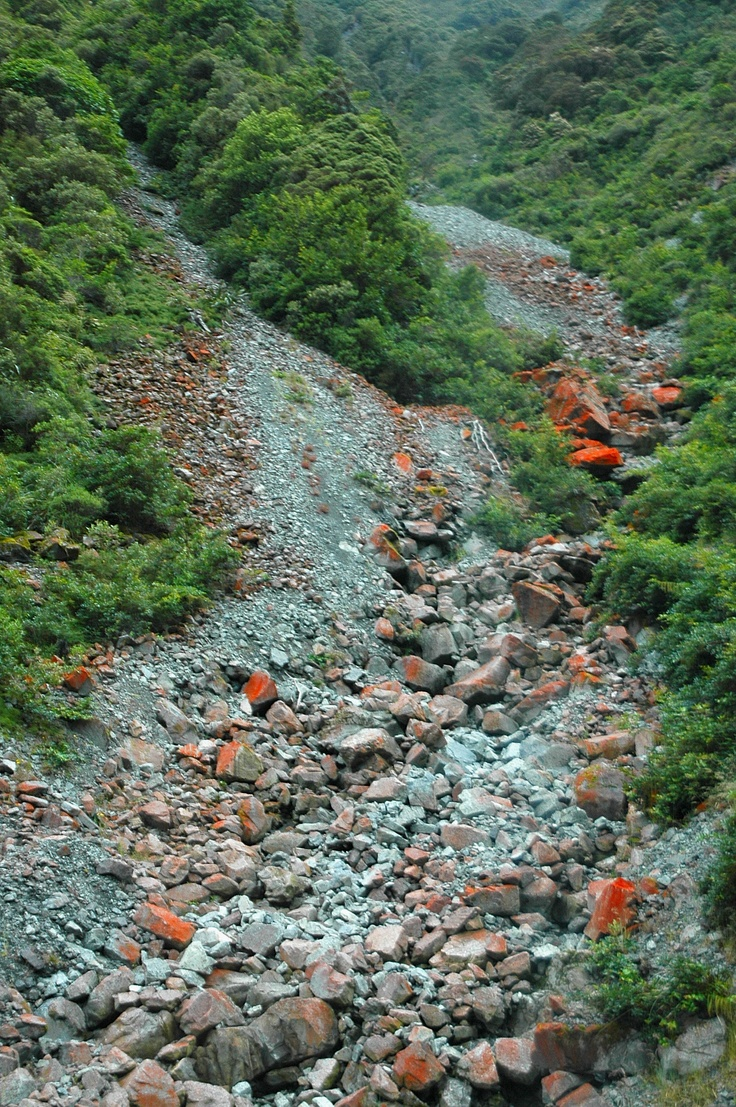 rocky stream in the mountains with red algae on the rocks