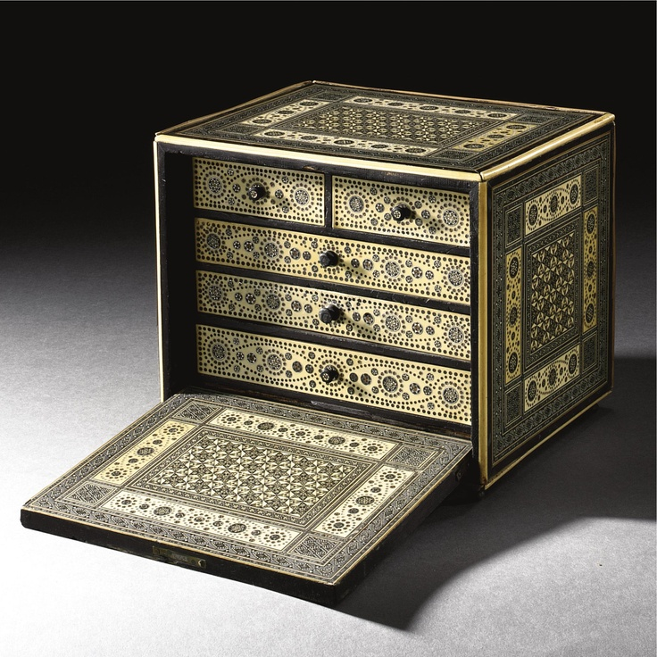 A FINE KATAMKARI BONE- AND SILVER-INLAID WOOD CABINET, SIND OR GUJARAT, CIRCA 18TH CENTURY of rectangular form on turned feet with a hinged drop-front revealing five drawers each with turned knobs, the wood body inlaid with bone, silver and lac, decorated throughout with katamkari or sadeli panels, roundels and stars