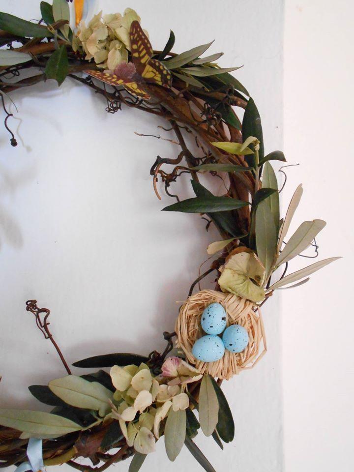Ghirlanda pasquale con tralci di vite, rami di olivo, nido di rafia con riproduzione di uova di Ghiandaia, farfalle (copie fotografiche in carta), nastri di raso, ortensie secche. Opera di Nella Tana di Biancaniglia