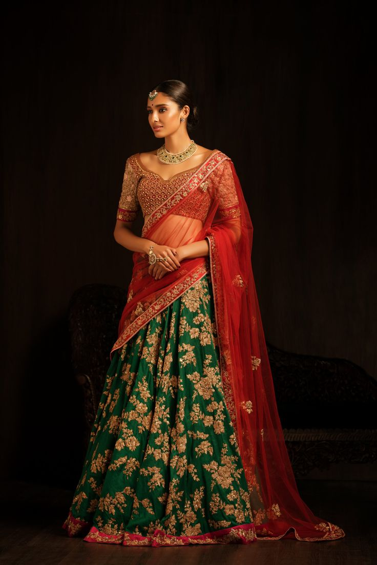 Classical bridal contrast with this dark green bias cut lehenga, sprayed with floral peeta embroidery all over
