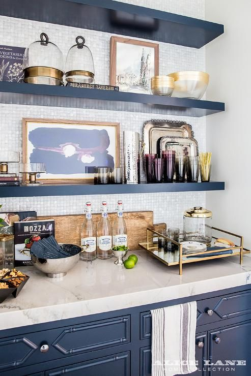 Blue butler's pantry features blue bamboo cabinets paired with a white marble countertop and a white iridescent tile backsplash lined with stacked blue floating shelves.