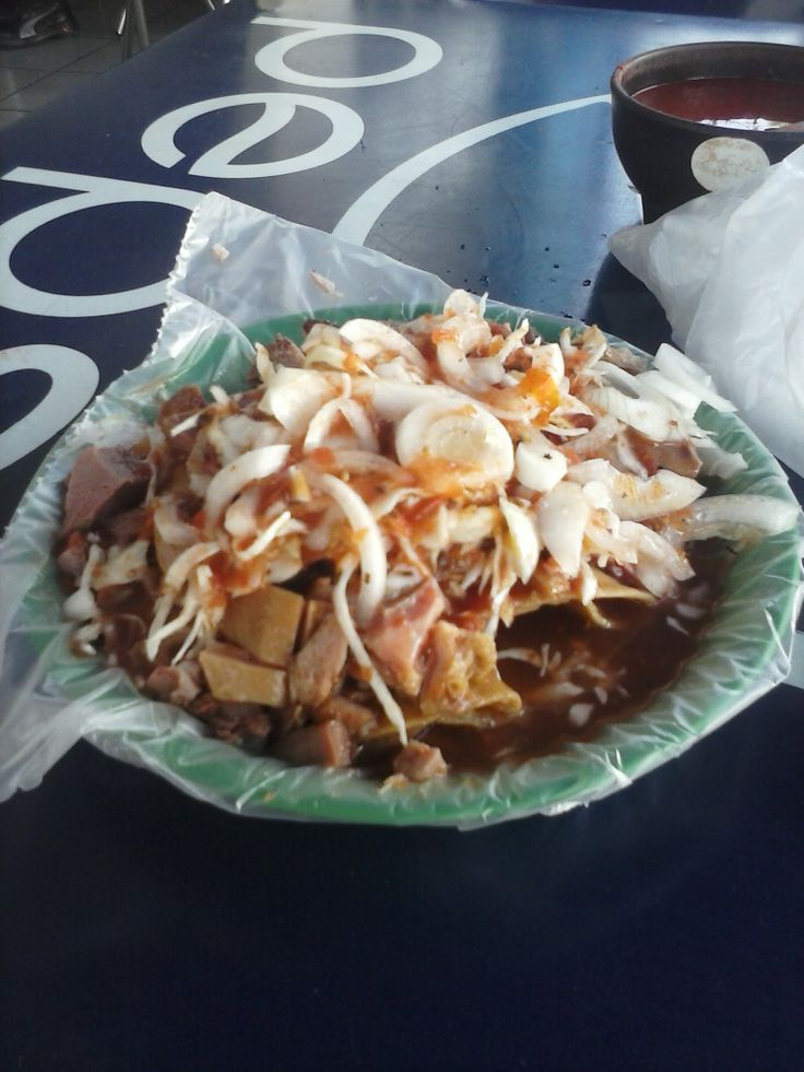 Tacos dorados de papa con carne(buche y maciza), bañados en salsa de jitomate, complementados con cebolla, col, chile de arbol y limon