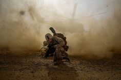 Cpl. Daniel Hopping, assaultman, Weapons Company, 1st Battalion, 7th Marine Regiment, and a native of Rogers, Arkansas, shields himself from dust being kicked up from a CH-53E Super Sea Stallion lifting off during a mission in Helmand province, Afghanistan, April 28, 2014.