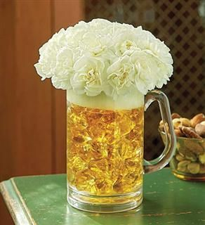 "Beer mug filled with amber-colored acrylic rocks.  White mini carnations form the ""foam."""